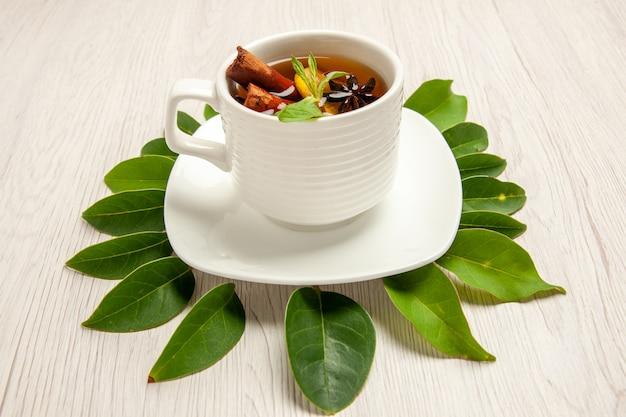 Tazza di tè con foglie verdi su bianco
