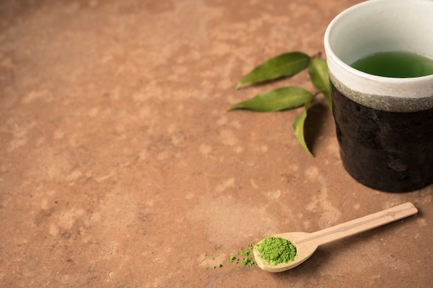 Cup of tea with green tea powder in wooden spoon on the table.