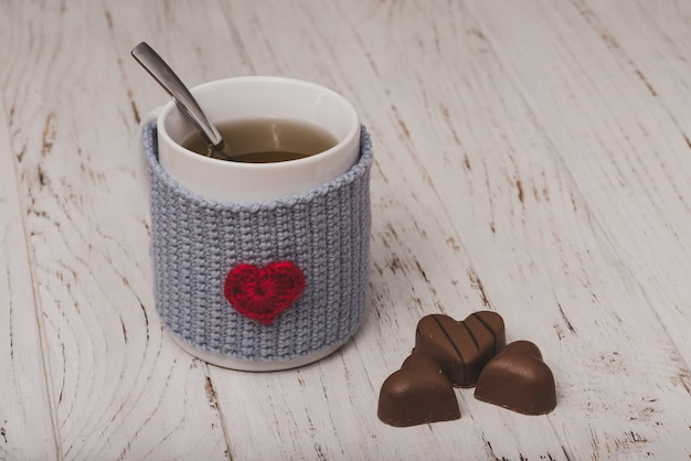 Cup of tea with heart-shaped chocolates