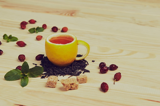 Cup of tea with hip roses, on wooden table. a cup made of real lemon