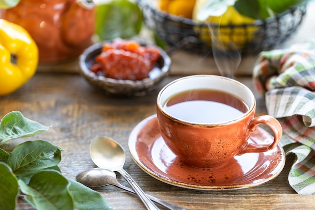 Cup of tea with homemade quince jam on an old wooden table. fresh fruits and quince leaves