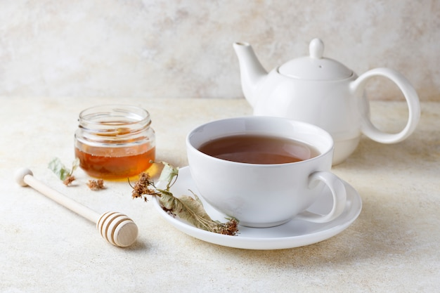 Cup of of tea with honey and teapot