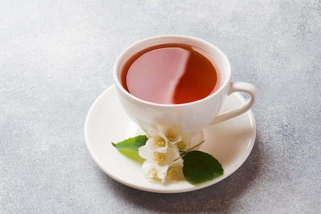 Cup of tea with jasmine flowers on a gray table