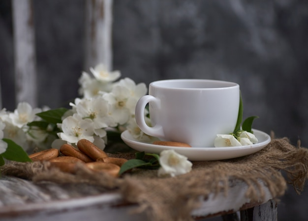 Cup of tea with jasmine flowers on a vintage chair
