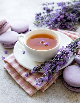 Cup of tea with lavender-flavored macaroon dessert and fresh lavender flowers