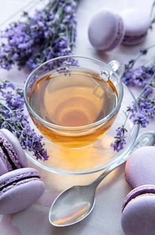 Cup of tea with lavender-flavored macaroon dessert on pink tiles background
