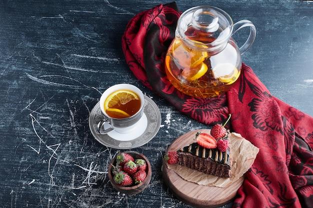 Una tazza di tè con torta al limone e cioccolato.