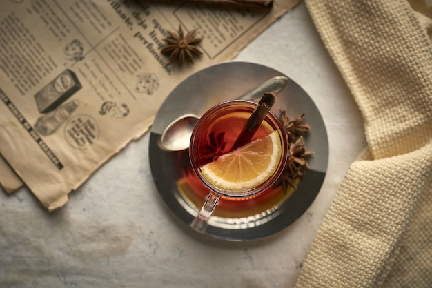 Cup of tea with lemon cinnamon sticks and cloves