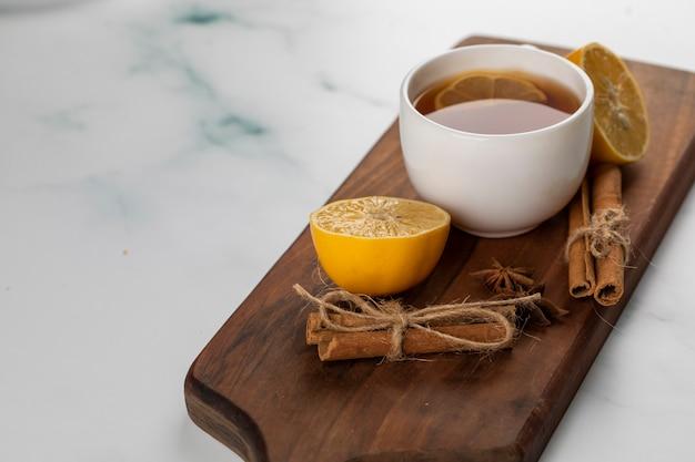 A cup of tea with lemon and cinnamon sticks.
