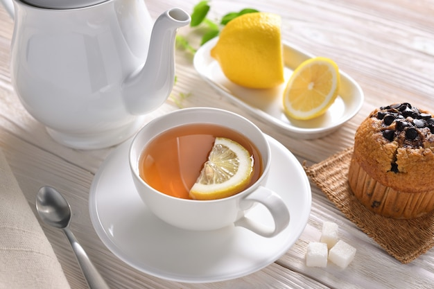 Cup of tea with lemon and cupcake on white table