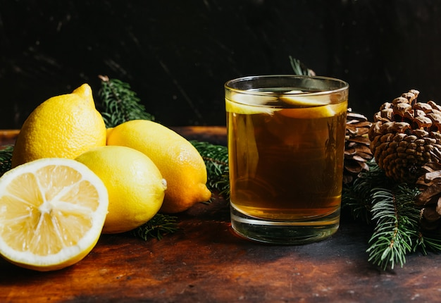 Cup of tea with lemon fruit lemons with fir branches for a rustic background. winter holidays