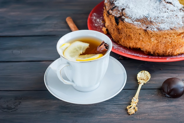Cup of tea with lemon and a fruit pie