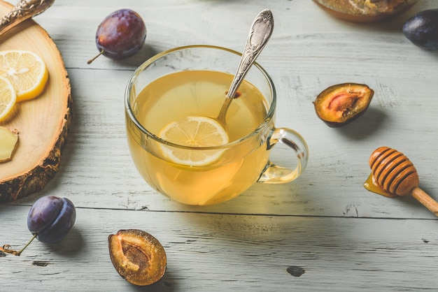 Cup of tea with lemon, honey and ginger over wooden surface