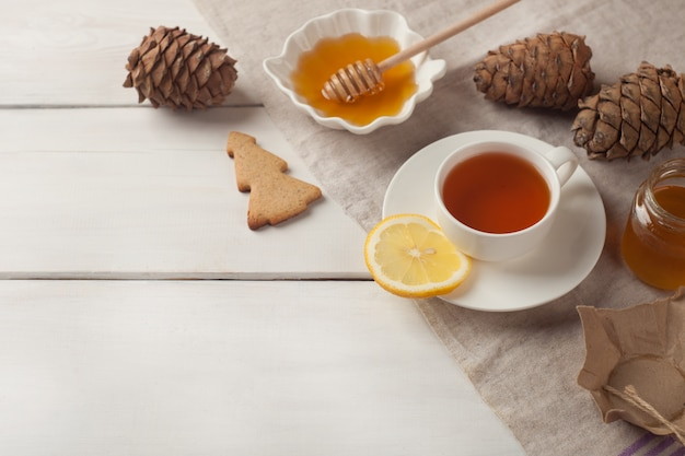 Cup of tea with lemon and honey on white wooden background