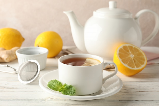 Cup of tea with lemon, mint, strainer, ginger and teapot on wooden, space for text