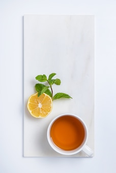 Cup of tea with lemon and mint on  white marble background. top view and copy space