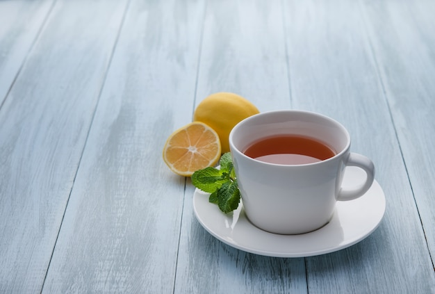 Cup of tea with lemon and mint on wooden blue background. close up and copy space