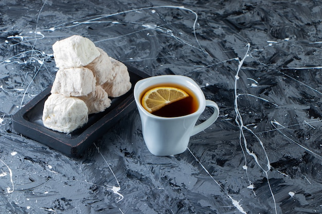 Cup of tea with lemon and plate of cotton candy on marble surface.