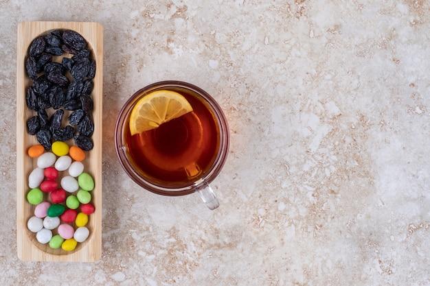 Tazza di tè al limone e piatto di dolci su superficie di marmo