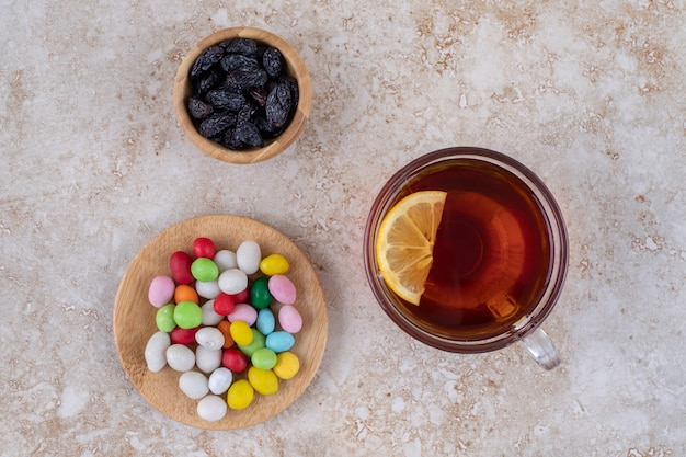 Cup of tea with lemon and plates of sweets on marble surface