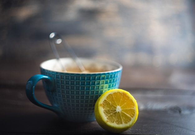 Cup of tea with lemon and spices on dark wooden background with copy space