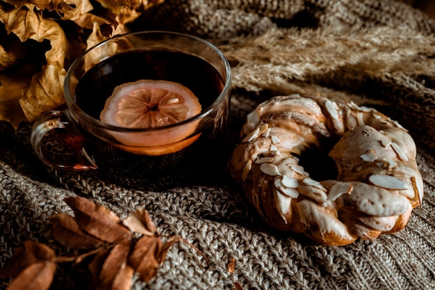 A cup of tea with lemon and sweet pastries with almonds lying on a knitted fabric autumn cozy home