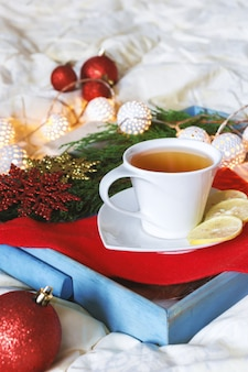 Cup of tea with lemon on a tray on the bed in bed winter morning comfort