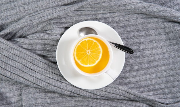 Cup of tea with lemon on a warm gray knitted background. a warming, hot winter cold drink.