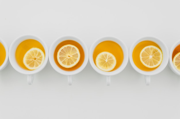 Cup of tea with lemons isolated on white background