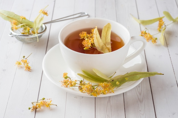 Cup of tea with linden flowers on a light table
