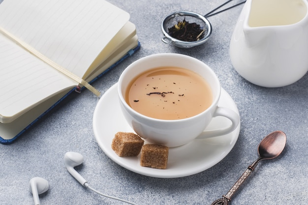 Cup of tea with milk, brown anise sugar and a notebook on a grey table.