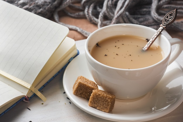 Cup of tea with milk, brown anise sugar and a notepad.