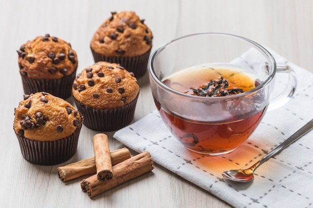 Cup of tea with muffins and cinnamon