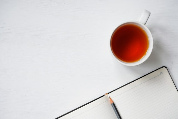 Cup of tea with notebook and pencil on white wooden table.