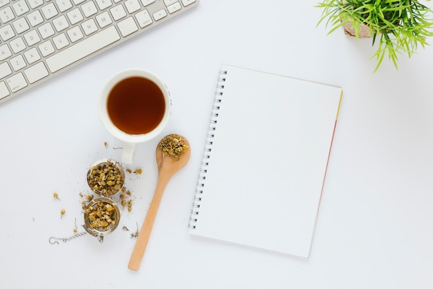 Cup of tea with notebook on white table
