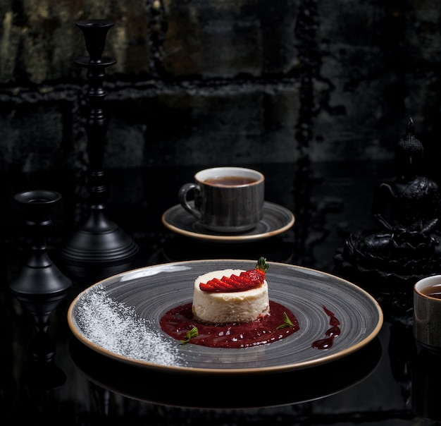 A cup of tea with ny cheesecake with berry sauce