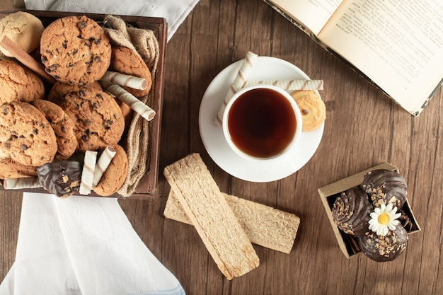 A cup of tea with oatmeal cookies and crackers. top view