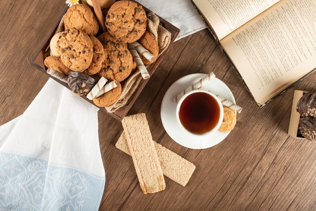 A cup of tea with oatmeal cookies and crackers on a wooden table