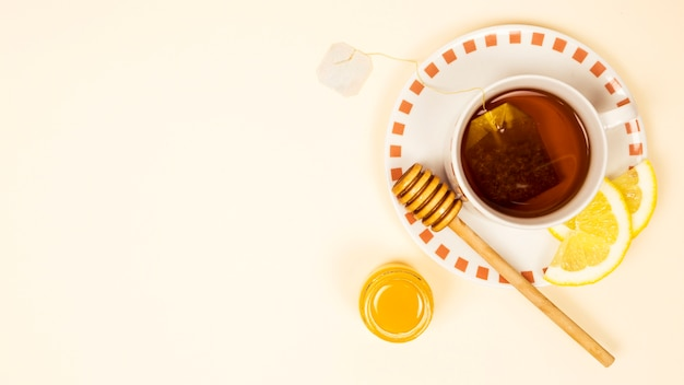 Cup of tea with organic lemon slice and honey on beige backdrop