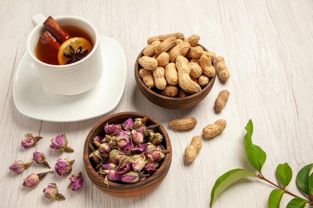 Tazza di tè con arachidi e fiori su bianco