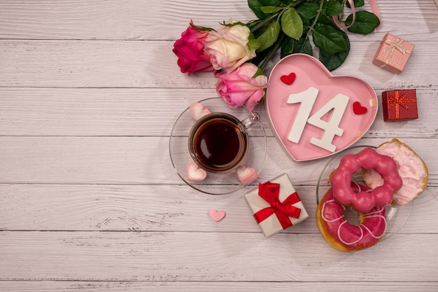 Cup of tea with pink roses on wooden table. valentine's day concept