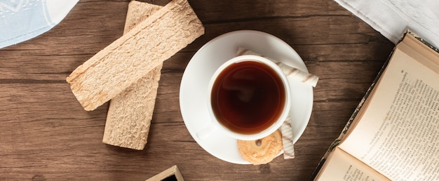 A cup of tea with some crispy crackers. top view