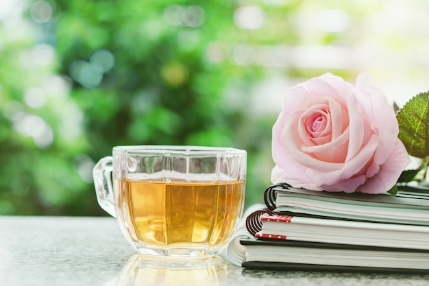 Cup of tea with spiral notebooks and sweet pink rose flower