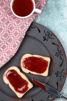 A cup of tea with a strawberry jam bread.