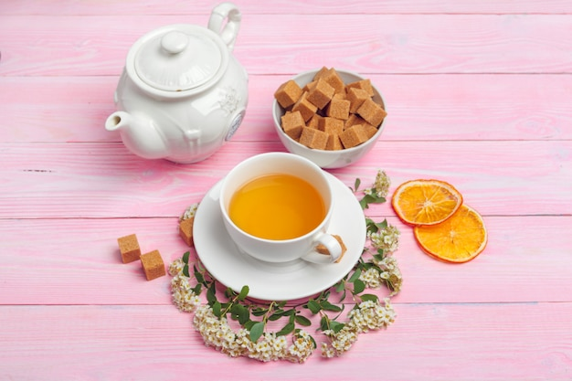 Cup of tea with sugar cubes and flower branches on wooden table close up