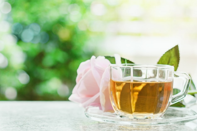 Cup of tea with sweet pink rose flower against blurred natural green background