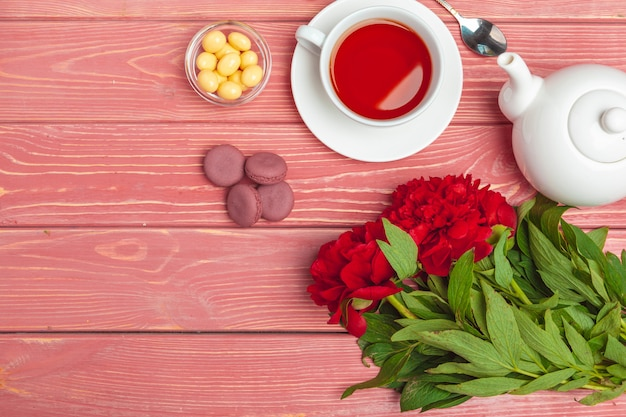 Cup of tea with sweets and flowers on wooden table