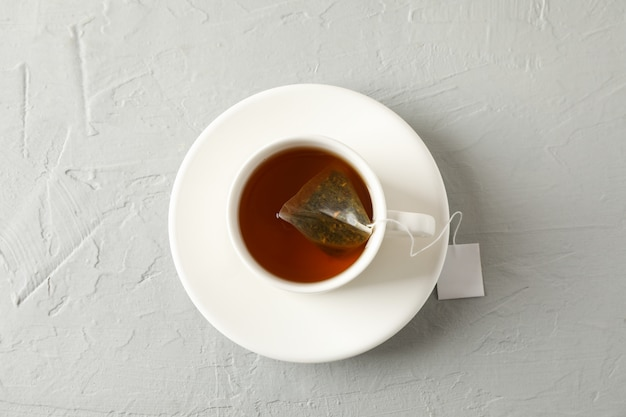 Cup of tea with tea bag on grey, top view