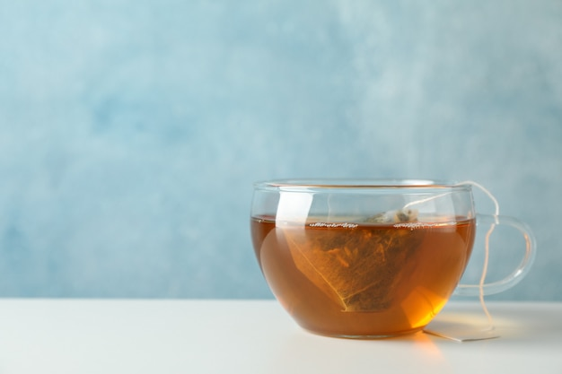 Cup of tea with tea bag on white, space for text