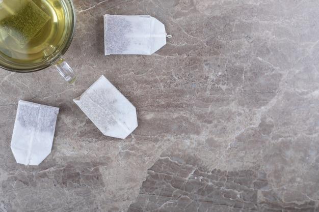 Tazza di tè con bustine di tè, sulla superficie del marmo